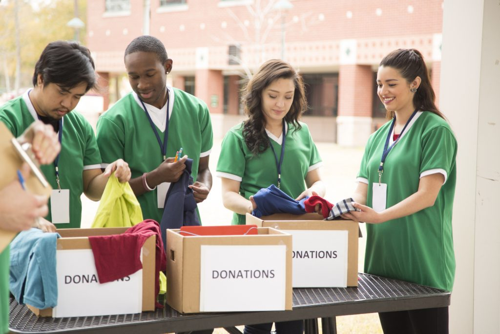 Organized group of multi-ethnic college student volunteers collect clothing donations for needy families in their community.
